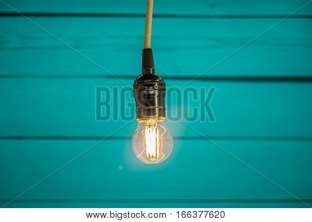 light bulb on blue wooden background copy space closeup