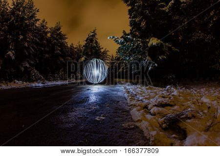 Futuristic glowing sphere on winter road and full moon light
