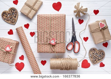 Flat lay Stylish composition with gift, scissors, wrapping paper and twine. Packaging of gifts on Valentine's Day, a birthday or Mother's Day. White wooden background with hearts and gifts. Top view.
