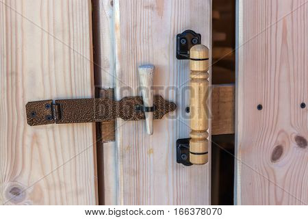 Latch. The door to the shed to store firewood. Fresh planks old and new latch.