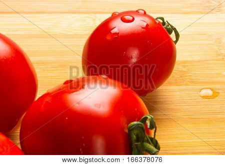 still life - ripe small tomatoes on wooden background