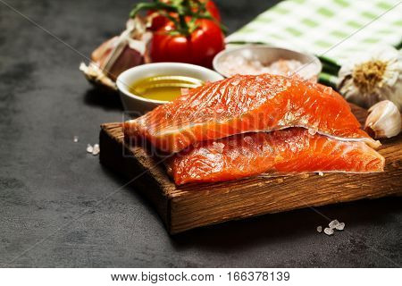 Tasty colorful Food Background with fresh Raw Fish Salmon and Cooking Ingredients - Olive Oil Salt Tomatoes Spaghetti and Spices on Old Metal Tray. Cooking Healthy Food Concept.