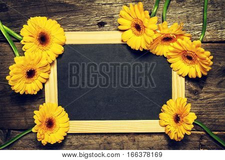 Beautiful Fresh Spring Yellow Gerbers on Old Vintage Wooden Table with Chalkboard. Top view with Copy Space. Spring Concept. Flower Background.