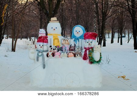 Four different size dressed in hats and scarfs snowmen and animals made of snow sit in white ice wagon near trees outdoors in winter