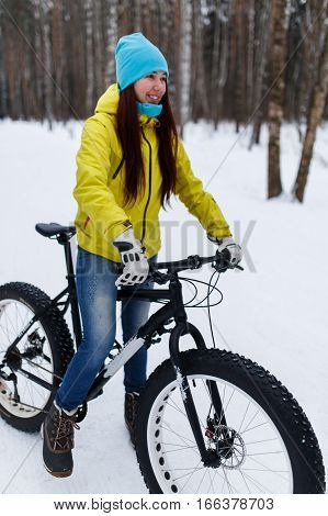 Young brunette in jeans on bicycle at winter forest