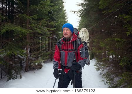 Smiling Man With Backpack Stands On The Trail