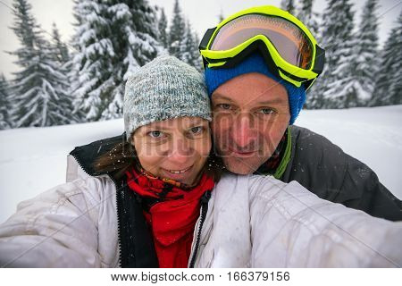 Happy couple of travelers taking selfie in the winter mountains during snowfall.