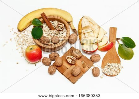 There are Banana,Apple,Walnuts in the Wooden Plate and Rolled Oats,Wooden Spoon,Trivet,with Green Leaves,Healthy Fresh Organic Food on the White Background,Top View
