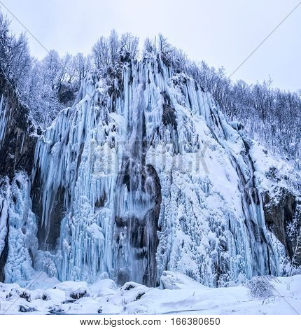 Frozen large waterfall in winter time at Plitvice lakes in Croatia.