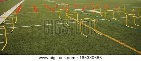Orange cones and yellow hurdles are set up on a green turf field for speed practice for high school sports.