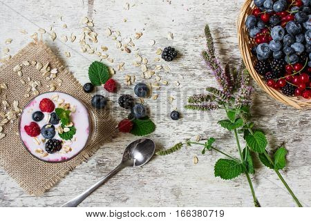 yogurt with fresh ripe berries oats and mint over white rustic background with a spoon and bowl with berries. healthy breakfast. top view