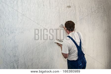 Hands plasterer at work. Application of the plaster on the wall