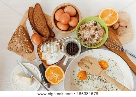Fried Eggs in the Frying Pan,Breakfast Ingredients.Orange,Bread,Butter,Porrige,Beans Coffe.Kitchen Accessories.Cooking Morning Food.White Table.