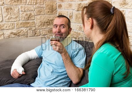 A man with a broken arm drinking a tea