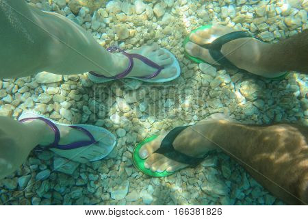 Top view of male and female feet in flip flops standing in clear water on rocky bottom of sea in sunny day.