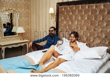 couple of young handsome bearded men one in white terry bathrobe laying on bed in hotel bedroom and watching tv with remote control holds coffee cup and other sitting in glasses