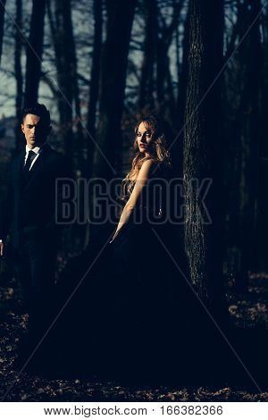 young couple of handsome man in black suit and bow with pretty sexy woman in elegant evening dress with skirt and long curly hair near tree in deep forest