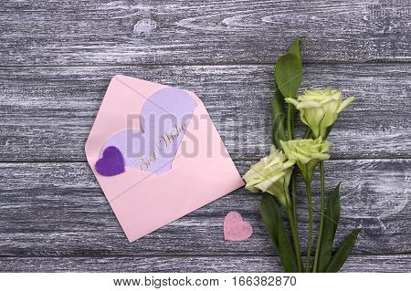 Flowers and hearts on wooden background. Greeting card. Conceptual photography. Wedding invitation card. Valentine day.