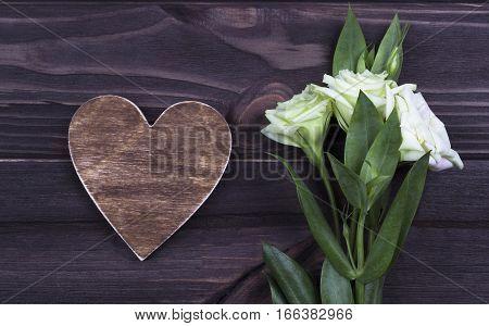 Brown wooden heart with flowers on dark background. Valentine Day. Greeting Card. Wedding