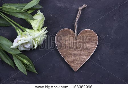 White flowers and brown wooden heart on dark concrete background.Greeting card. Wedding invitation concept. Valentines day.