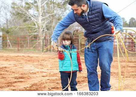 Father Learning Son Making Loop And Throwing Lasso In Ranch