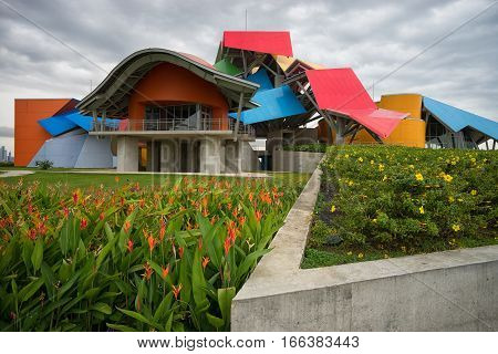 June 13, 2016 Panama City, Panama: the colourful building of Biomuseum with blooming flowers in the front