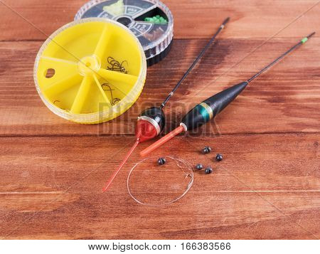 The floats sinkers fishing line with hooks and small round box on a wooden background.