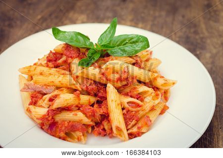 Italian Wholemeal Pasta Penne with Tuna and Basil. Fresh pasta with tuna and tomato sauce on old wooden background. Italian cuisine concept. Selective focus.