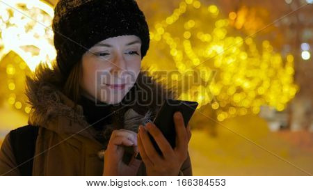 Young pretty woman using smartphone in the city at night. Christmas, winter, technology and holiday concept