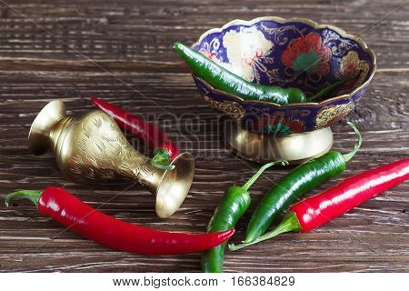 Red and green pepper on a wooden background in rustic style