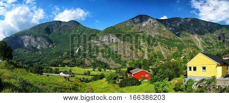 Picturesque village with small houses cottages on hilly rocky mountains covered with green trees and grass on sunny summer day on cloudy blue sky background