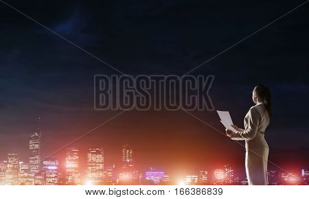 Rear view of elegant businesswoman with paper sheet against night city