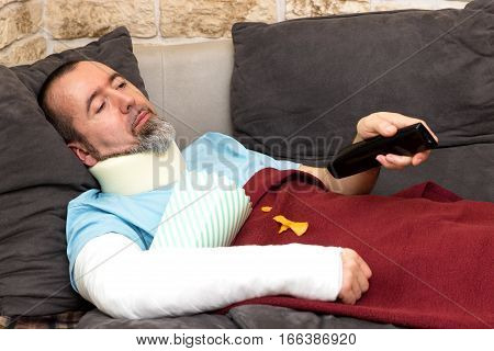 Injured man lies on the couch and watches television