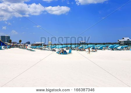 Clearwater, FL - April 21: People sitting under blue umbrellas on Clearwater beach in Florida