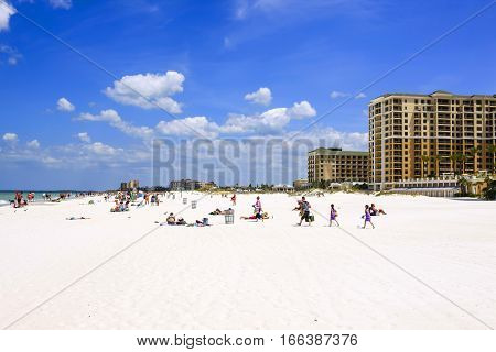 Clearwater, FL - April 21: People on Clearwater beach FL with waterfront hotels in the background