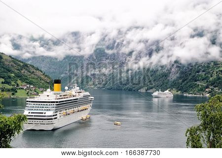 Norway - January 25 2010: cruiser ship or liner in fjord bay or harbor calm water surrounded by mountains on rocky sea shore covered with green trees on summer day on cloudy white sky
