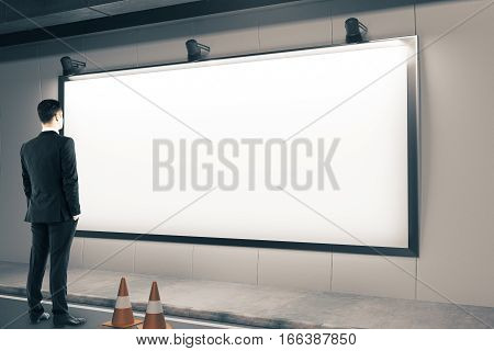 Businessman looking on blank poster and traffic cone on road. Mock up 3D Rendering