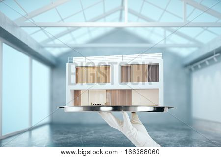 Hand holding silver trey with modern house in concrete interior. Property concept. 3D Rendering
