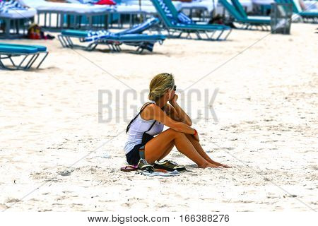 Clearwater, FL - April 21: Woman sitting alone on Clearwater beach in Florida