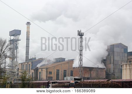 Processing sugar beet in sugar refinery. Factory chimneys emitting smoke to the air.