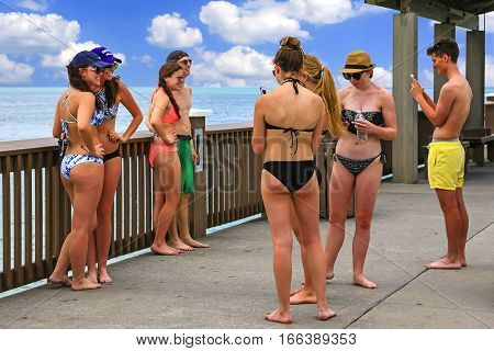 Clearwater, FL - April 21: Spring break students in a group on Clearwater beach pier in Florida