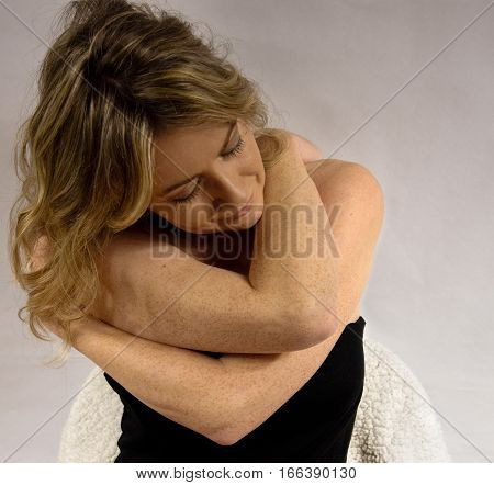Woman With Freckles With Arms Wrapped Around Herself