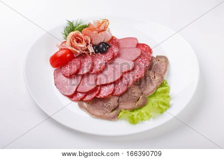 Sliced homemade dry sausages and meat products cured meat bacon with fresh cucumber slices on a white plate. Isolated on white background close-up top view.