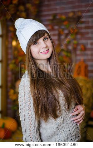 Closeup portrait pretty girl with long hair and snow white smile in knitted hat with camera. She is smiling to side and happy