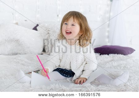 Smiling little girl drawing in bed ?olored pencils