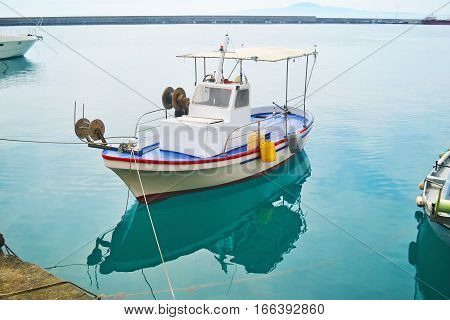 fishing boat reflected on sea at Kalamata port Peloponnese Greece
