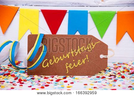 Brown Label With German Text Geburtstagsfeier Means Birthday Celebration. Party Decoration Like Streamer And Confetti. White Wooden Background. Greeting Card For Celebrations