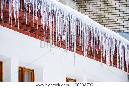 Ice icicles hanging from the eaves of the roof of the house. Winter thaw