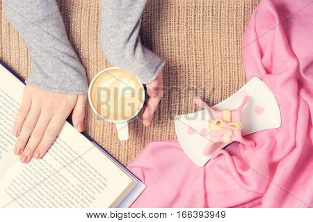Girl Reading Book And Holding Cup Of Coffee With Latte Art. Valentines Day And Leasure Time Concept.