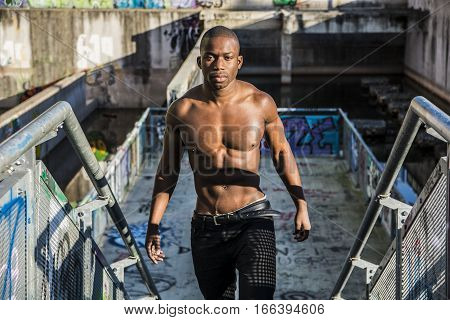 Portrait of a hot black man shirtless in urban environment, walking on metal stairs, looking at camera